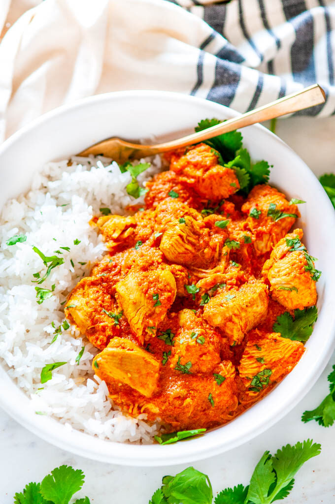 Instant Pot Chicken Tikki Masala in white bowl with basmati rice, cilantro and gold fork