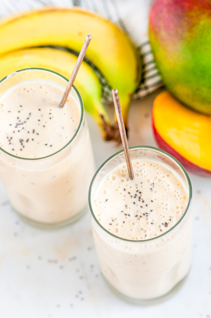 Banana Mango Coconut Smoothie in glasses with chia seeds and spoons om white marble