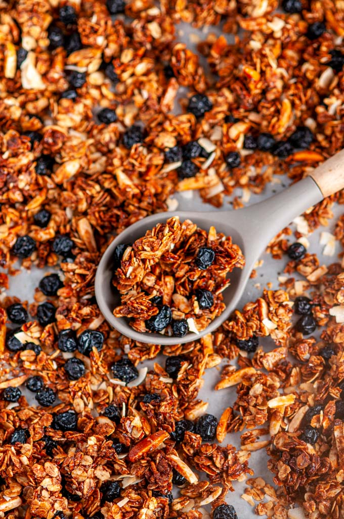 Blueberry Almond Coconut Granola on baking sheet with gray spoon close up