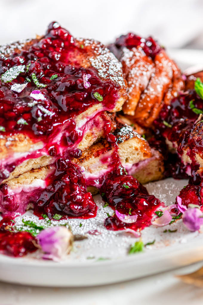 Cream Cheese Stuffed Blackberry Compote French Toast on gray plate with flowers and gold fork close up