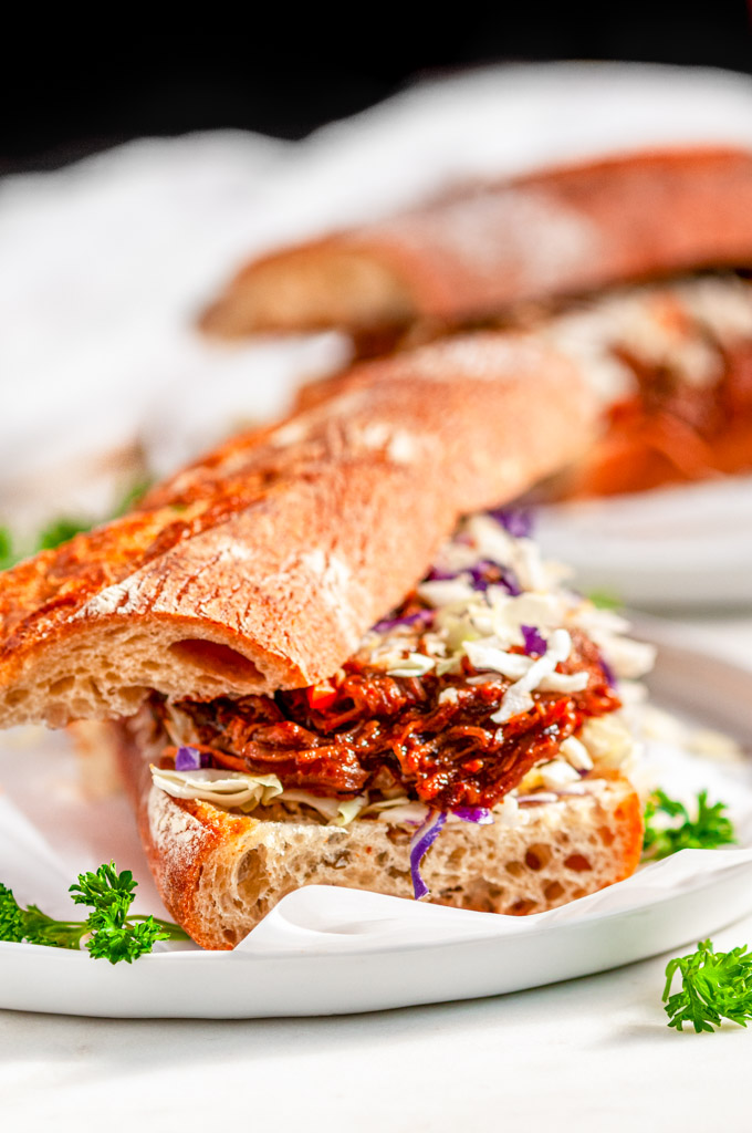 Instant Pot Pulled Pork Sandwiches on baguette with coleslaw mix on gray plate and white marble close up