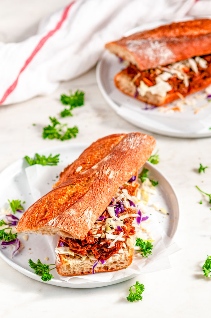 Instant Pot Pulled Pork Sandwiches on baguette with coleslaw mix on gray plate and white marble