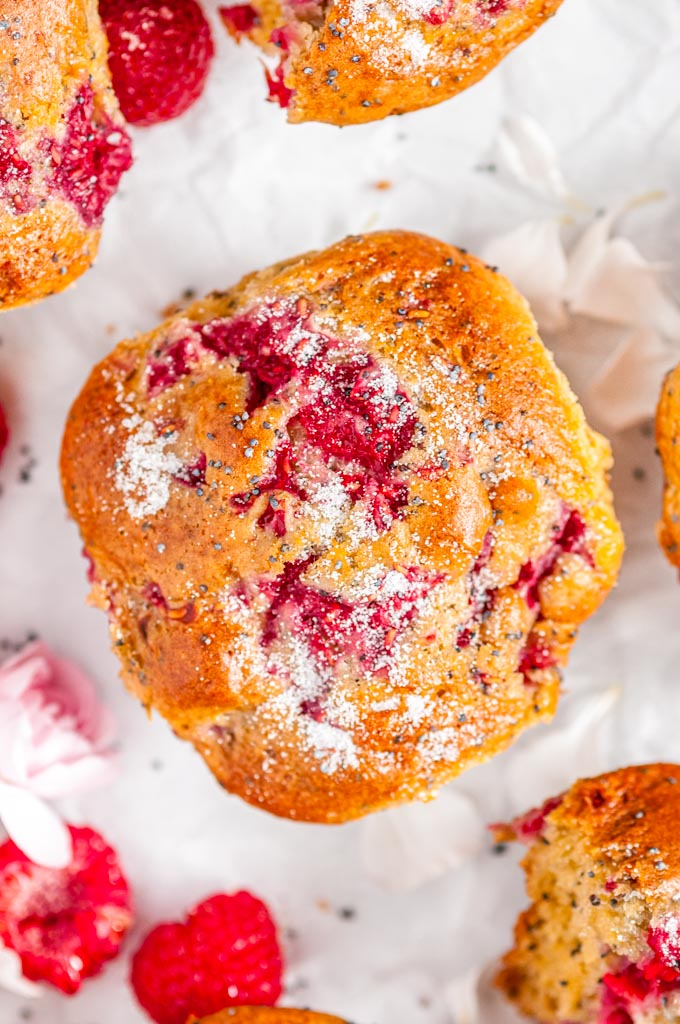 Raspberry Poppy Seed Muffins with pink and white flowers on parchment close up