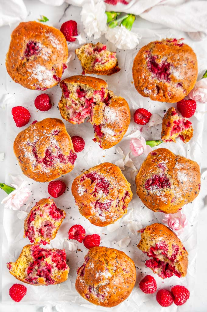 Raspberry Poppy Seed Muffins with pink and white flowers on parchment and white marble