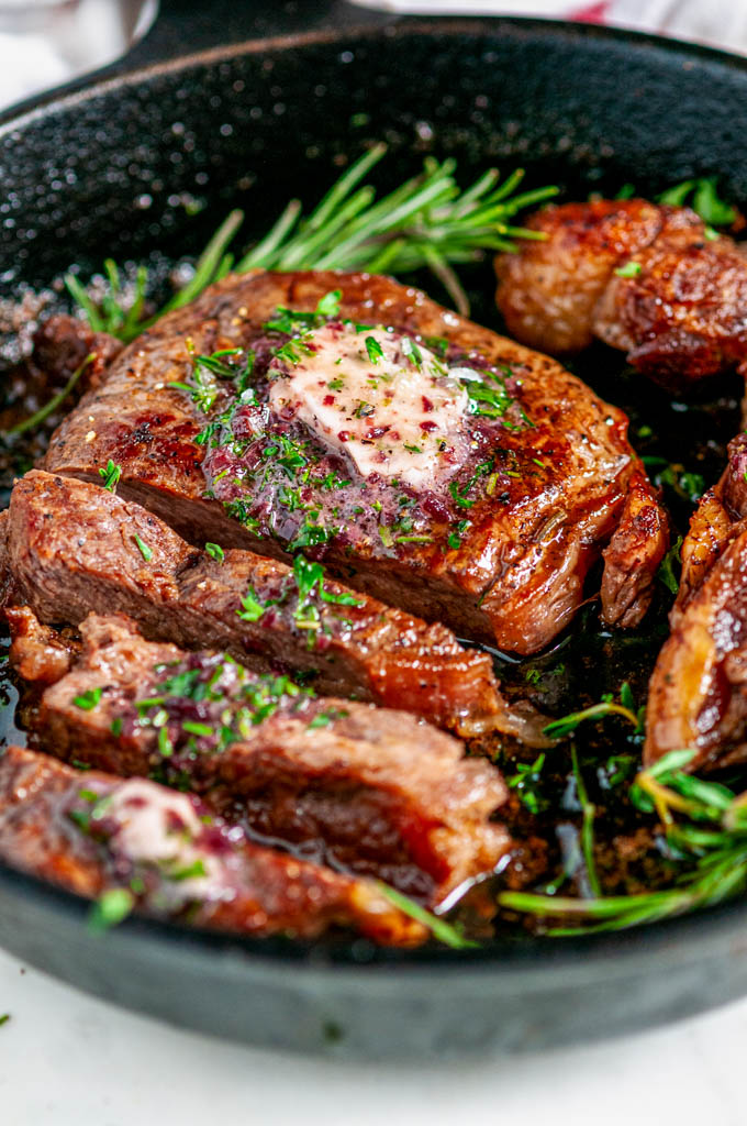 Rib Eye Steak with Red Wine Shallot Compound Butter and herbs sliced in cast iron skillet close up