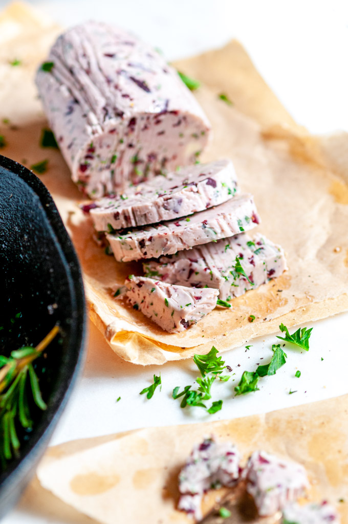 Rib Eye Steak with Red Wine Shallot Compound Butter and herbs sliced close up