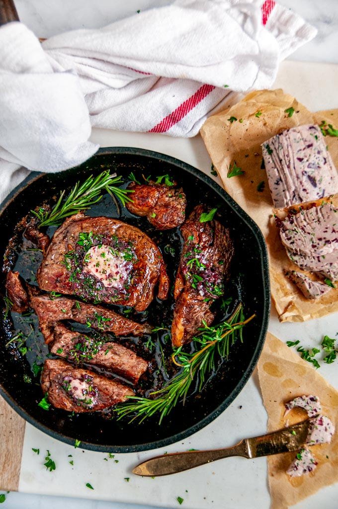Rib Eye Steak with Red Wine Shallot Compound Butter and herbs sliced in cast iron skillet