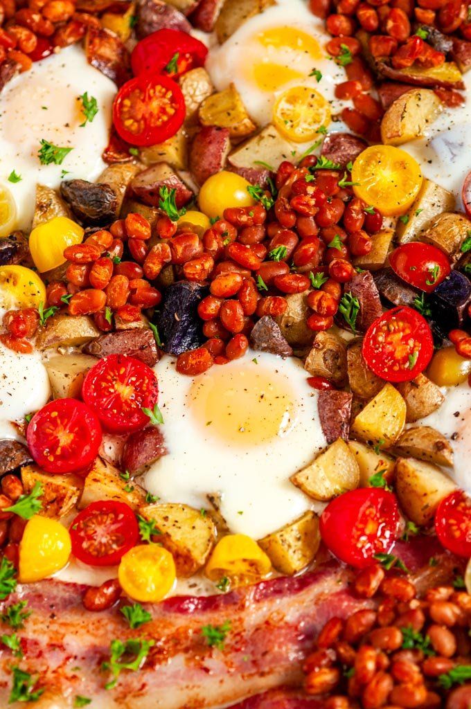 Sheet Pan Full English Breakfast with sausage, bacon, eggs, tomatoes, baked beans, and potatoes close up