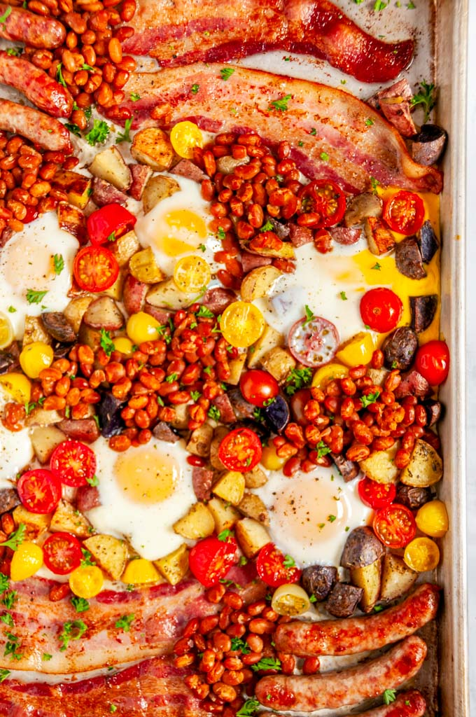 Sheet Pan Full English Breakfast with sausage, bacon, eggs, tomatoes, baked beans, and potatoes on white marble