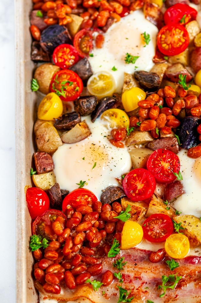 Sheet Pan Full English Breakfast with sausage, bacon, eggs, tomatoes, baked beans, and potatoes on white marble close up