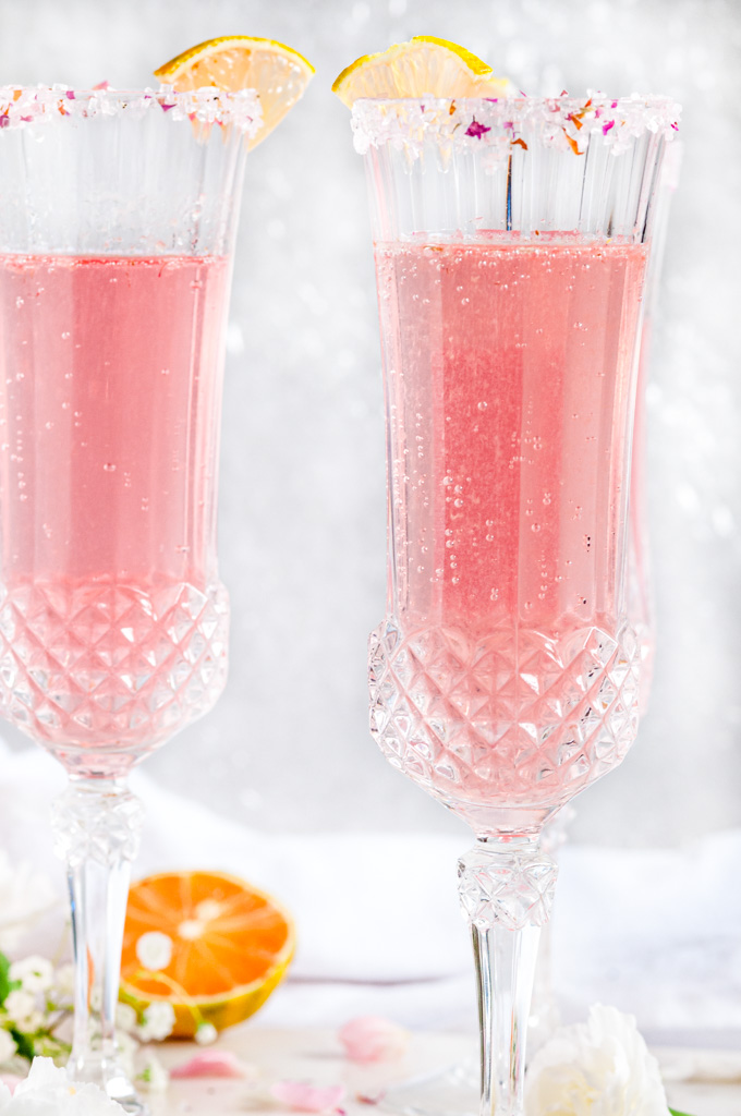 Sparkling Raspberry Rose Spritzer in crystal sugar rimmed glasses with variegated lemon slices on white marble close up