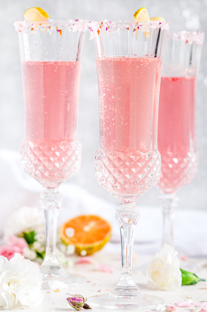 Sparkling Raspberry Rose Spritzer in crystal sugar rimmed glasses with variegated lemon slices on white marble