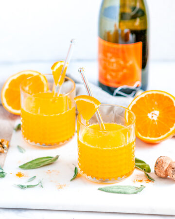 Immune Boosting Orange Turmeric Cocktail in glasses with fresh sage, prosecco bottle, and tea towel on white marble