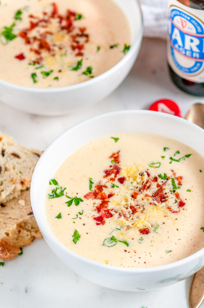 Irish Cheese Beer Soup in white bowls with gold spoons and soda bread on marble close up