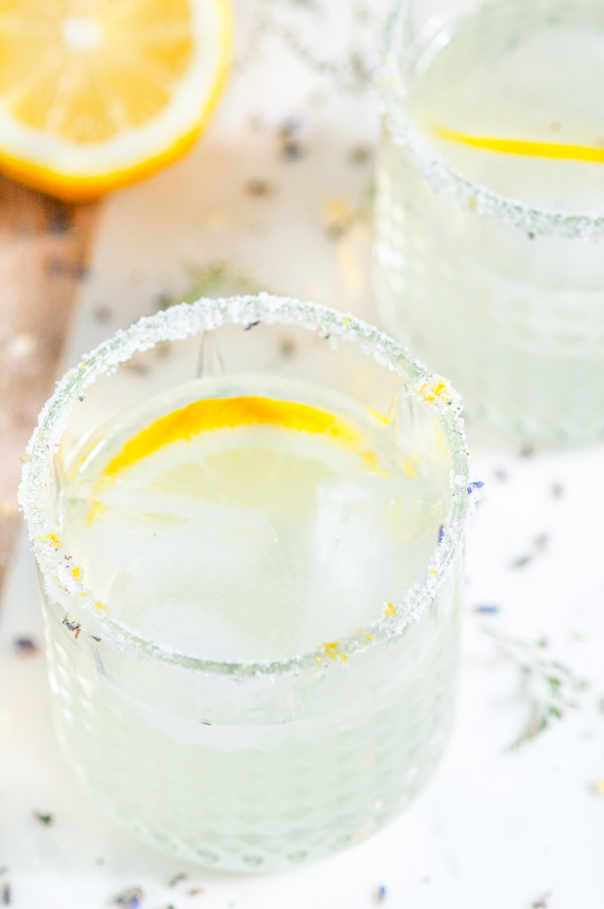 Lavender Collins Cocktail with lemons on white marble close up