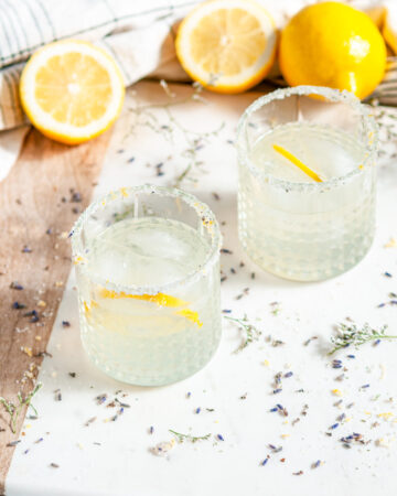 Lavender Collins Cocktail with lemons and soda bottles on white marble
