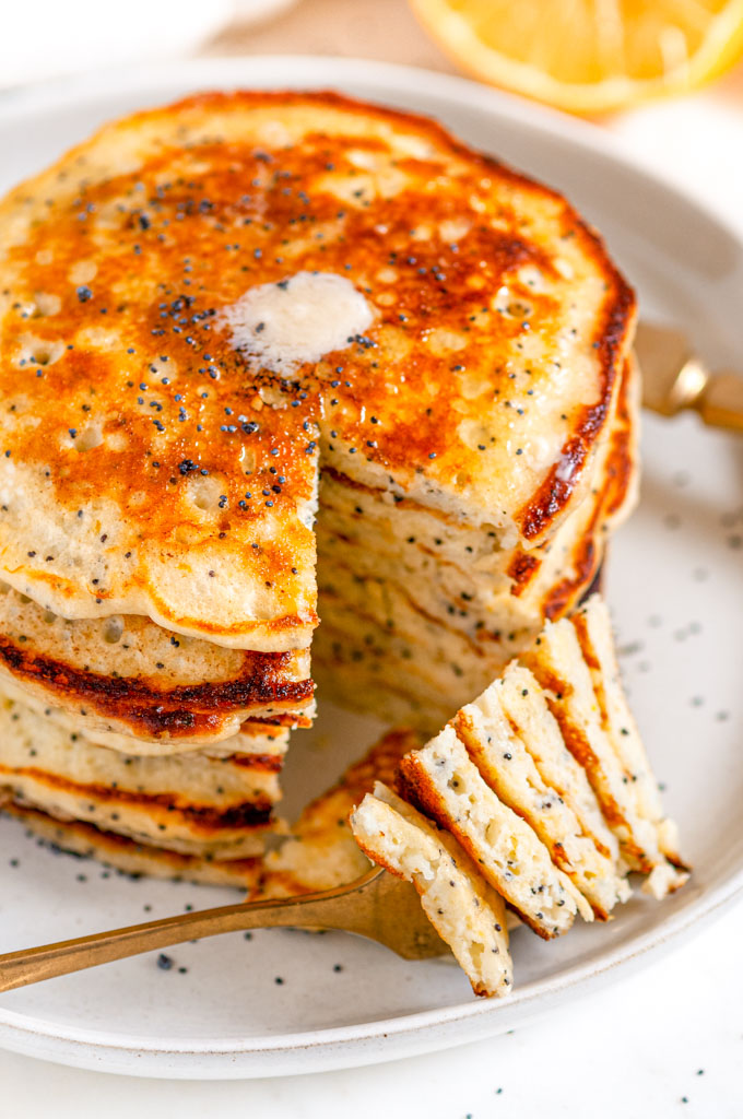Lemon Poppy Seed Buttermilk Pancakes gold fork bite with butter on gray plate close up