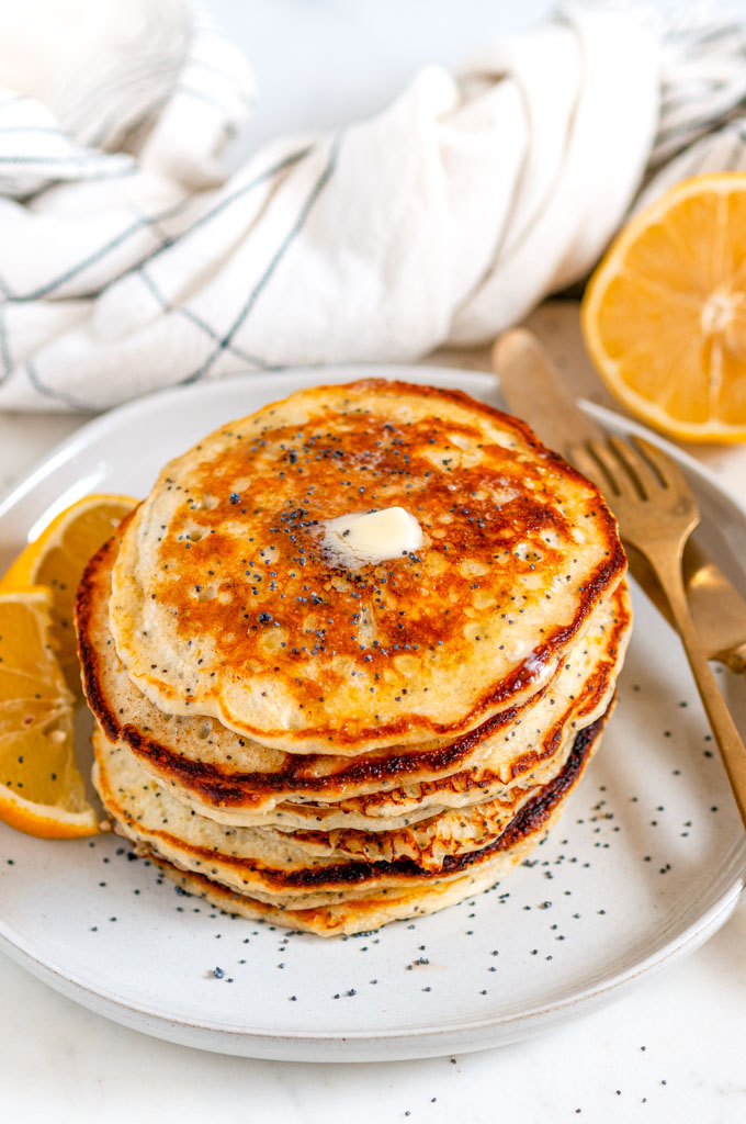 Lemon Poppy Seed Buttermilk Pancakes on gray plate with butter, gold fork and knife, and tea towel