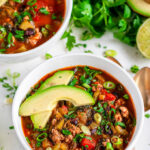 One Pot Turkey Chili in white bowls with gold spoons, avocado, cilantro and limes on marble