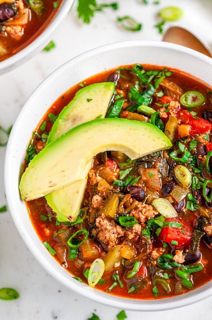 One Pot Turkey Chili in white bowl with avocado, cilantro and lime on marble close up