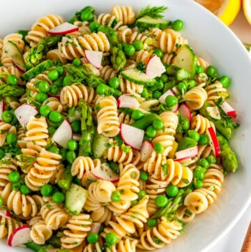 Springtime Vegetable Pasta Salad in white bowl with lemons and wooden serving spoon on marble