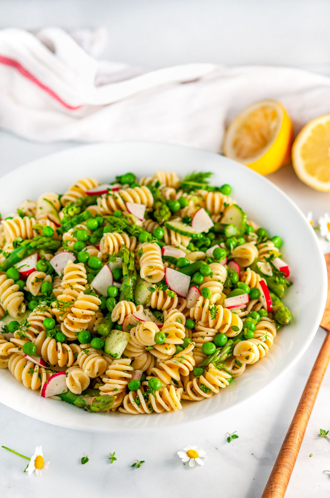 Springtime Vegetable Pasta Salad in white bowl with lemons, wooden serving spoon, and tea towel on marble
