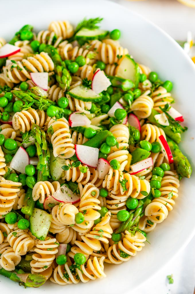 Springtime Vegetable Pasta Salad in white bowl on marble close up