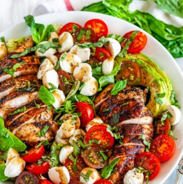 Balsamic Chicken Caprese Salad in white bowl with tongs on marble