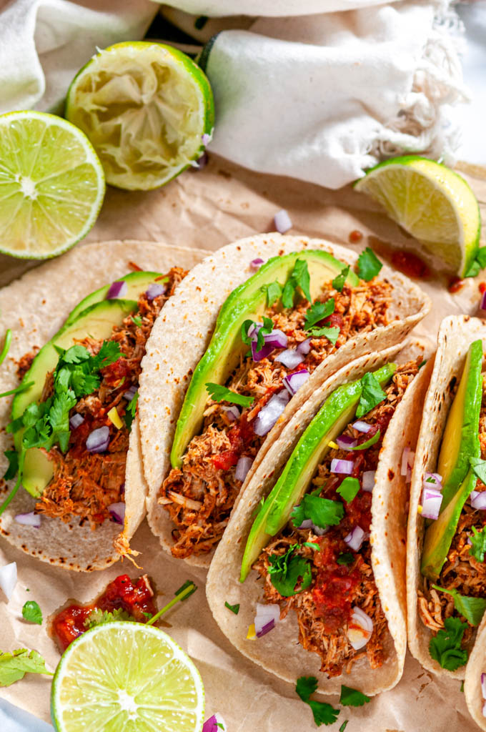 Instant Pot Chicken Tinga tacos with avocado, limes, red onion and cilantro on brown parchment