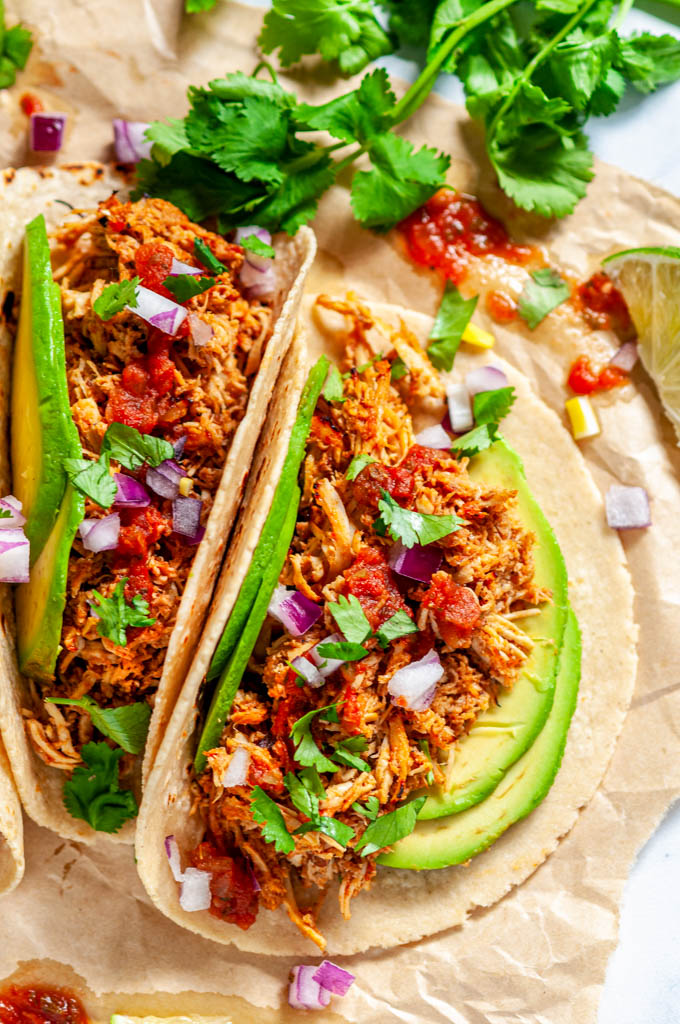 Instant Pot Chicken Tinga tacos with avocado, limes, red onion and cilantro on brown parchment close up