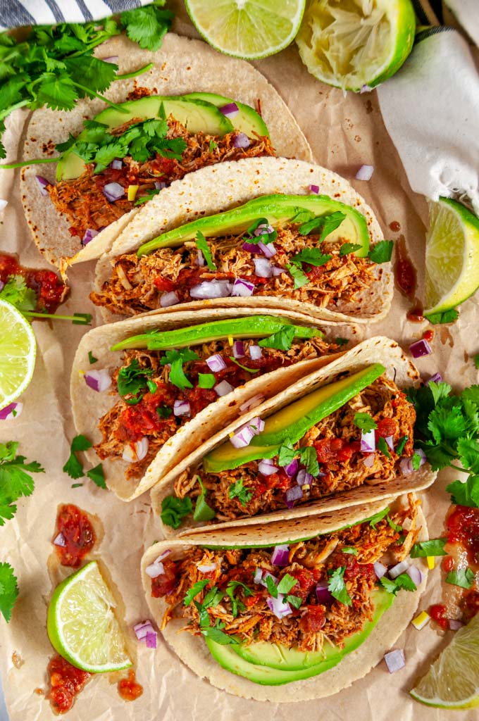 Instant Pot Chicken Tinga tacos with avocado, limes, red onion and cilantro on brown parchment over head