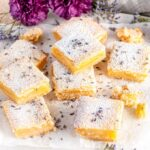 Lavender Lemon bars with powdered sugar and purple flowers on parchment
