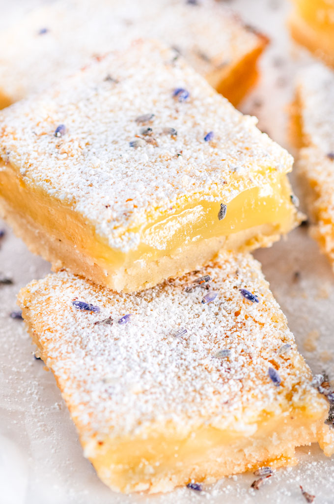 Lavender Lemon bars with powdered sugar and purple flowers on parchment close up
