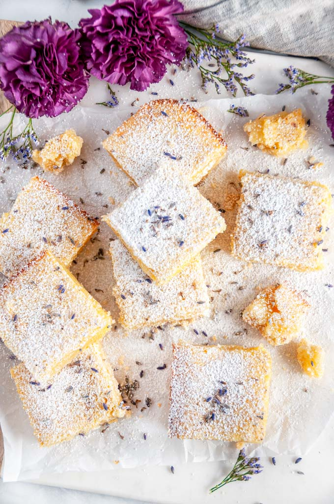 Lavender Lemon bars with powdered sugar and purple flowers on parchment overhead