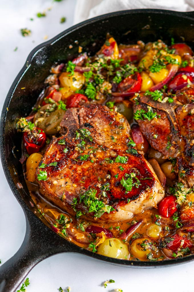 Skillet Balsamic Pork Chops with Tomatoes and Gremolata in black cast iron lodge skillet on white marble close up