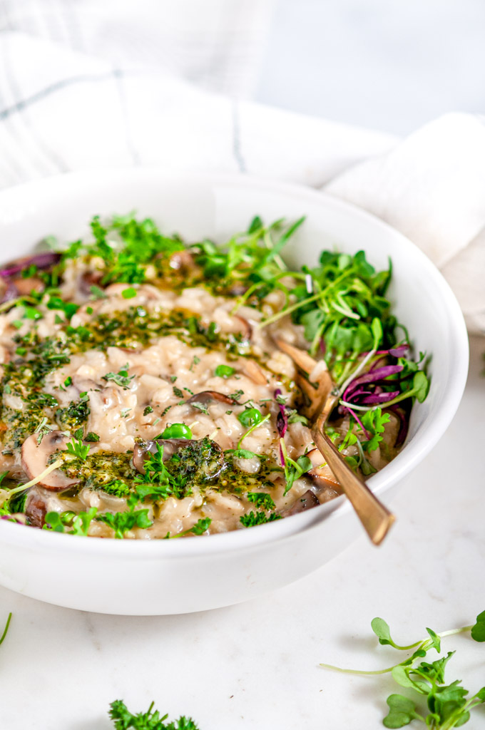 Spring Herb Mushroom Risotto with microgreens in white bowl with gold fork and tea towel on white marble close up