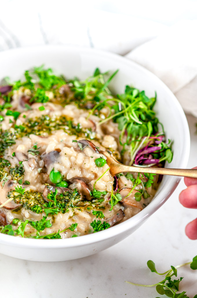 Spring Herb Mushroom Risotto with microgreens in white bowl with gold fork in hand and tea towel on white marble close up