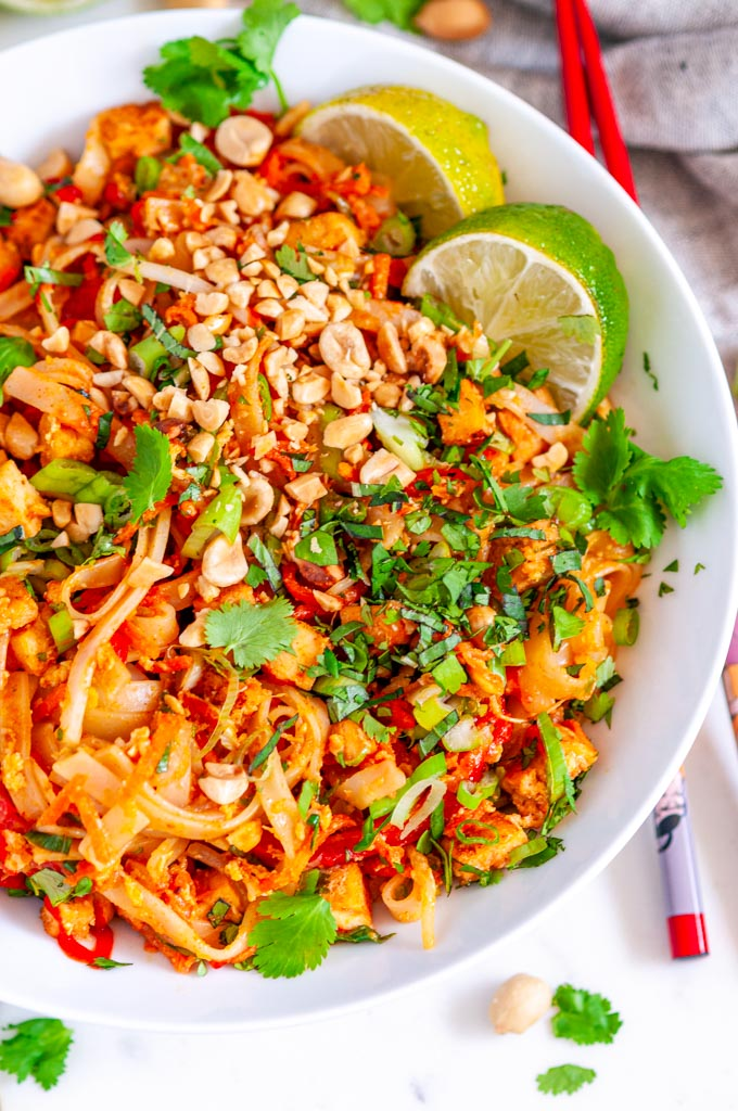 Tofu Pad Thai with lime slices, and peanuts in white bowl with gray tea towel on white marble close up