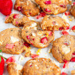 White Chocolate Strawberry Rhubarb Cookies on white parchment and marble with lemon zest close up