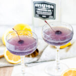Classic Aviation Cocktail in crystal glasses with brandied cherries, lemon and Aviation Gin bottle on white marble