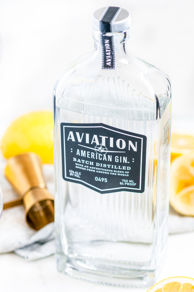 Classic Aviation Cocktail Aviation Gin bottle with lemon and gold jigger on white marble