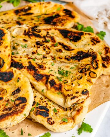Easy Homemade Naan Bread with cilantro and tea towel on white marble and parchment