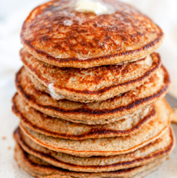 Fluffy Banana Oat Pancakes (Gluten Free) stack with butter on top side view close up