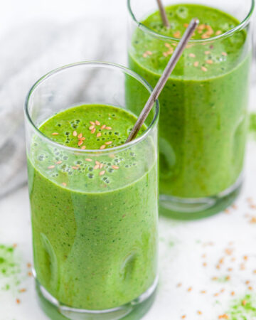 Green Tea Matcha Smoothie in tall glasses with flax seeds and silver spoons over head side view