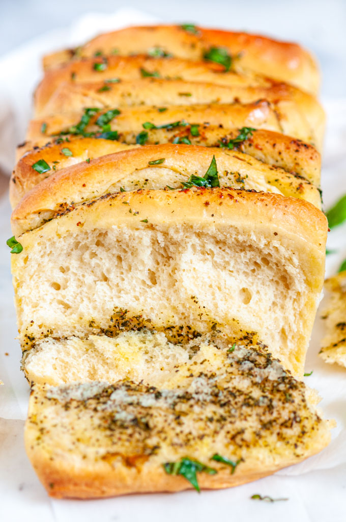 Pull Apart Pesto Bread one slice cut with basil on wood and white marble board close up