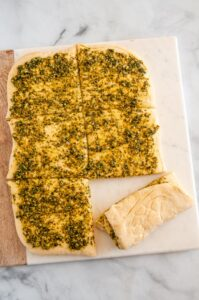 Pull Apart Pesto Bread dough unbaked on wood and marble board over head sliced into squares with one roll