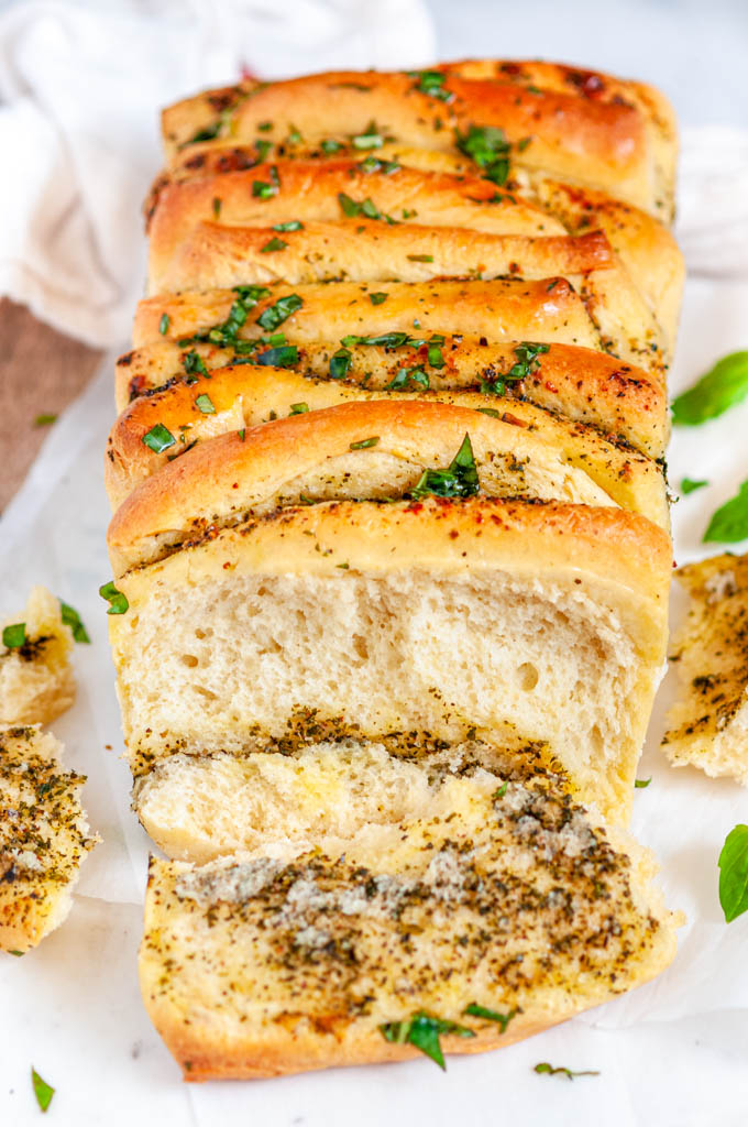 Pull Apart Pesto Bread one slice cut with basil on wood and white marble board
