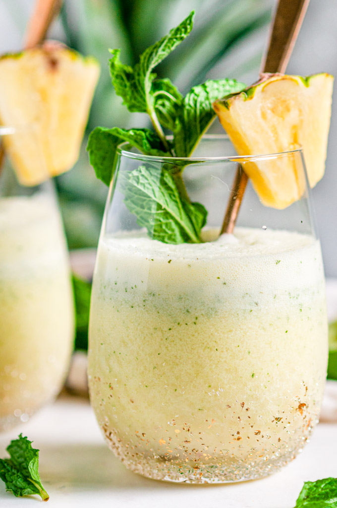 Skinny Piña Colada Cocktail in gold speckled stemless wine glasses with gold spoons and fresh mint on white marble close up side view