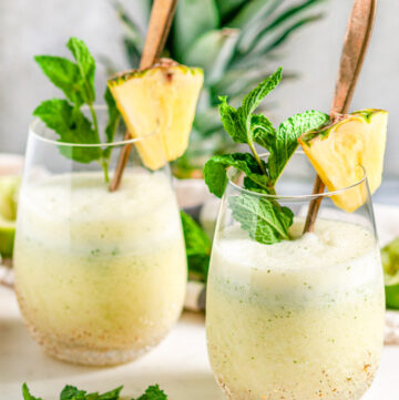 Skinny Piña Colada Cocktail in gold speckled stemless wine glasses with gold spoons and fresh mint on white marble side view