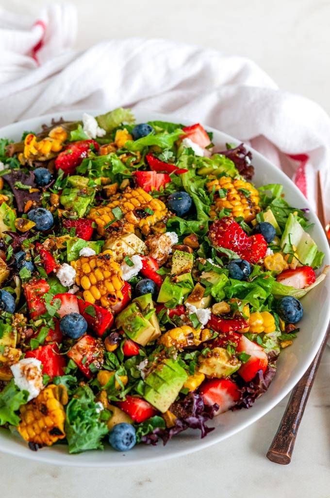 Strawberry Avocado Corn Salad in white bowl with copper silverware side view